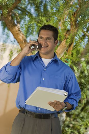 Man with Binder Talking on Cell Phone