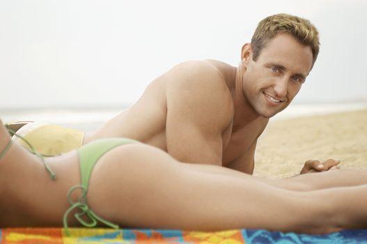 Man Lying Next to Girlfriend on Beach