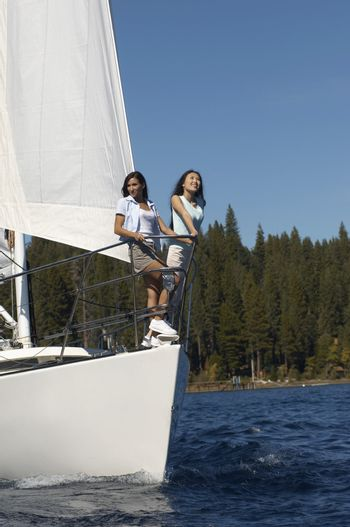 Friends Standing on Bow of Sailboat