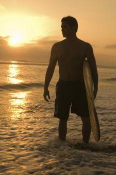 Surfer among Waves at Sunset