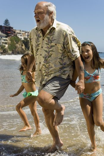 Girls Running Through Waves with Grandfather