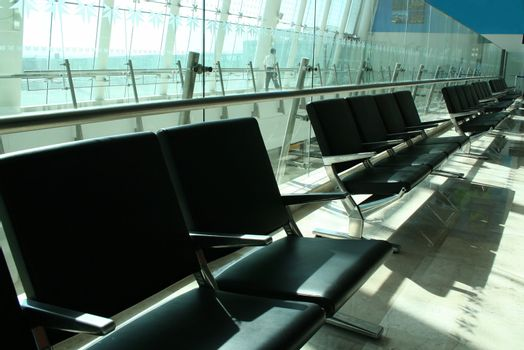 Empty seats at airport with security in background