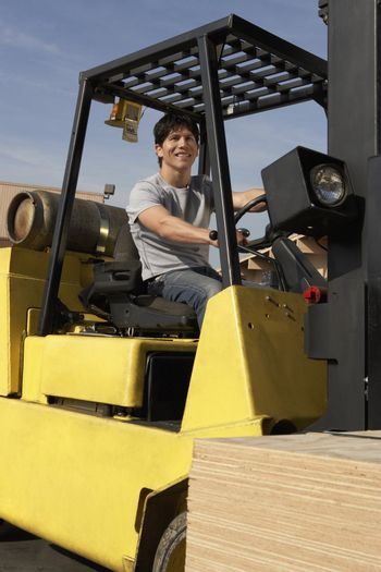 Forklift Driver on Forklift with Stack of Lumber