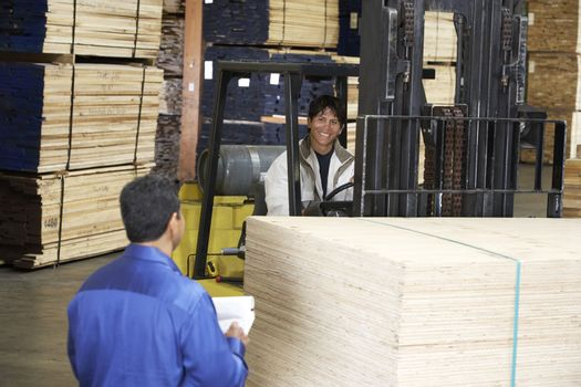 Forklift Driver with Manager in Lumber Warehouse