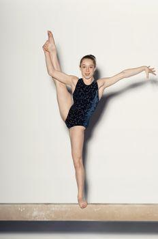 Teenaged Gymnast Standing on One Leg on Balance Beam