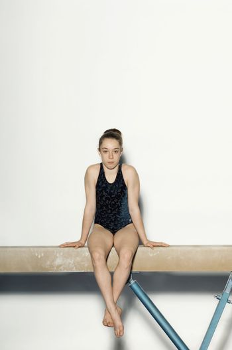Teenaged Gymnast Sitting on Balance Beam