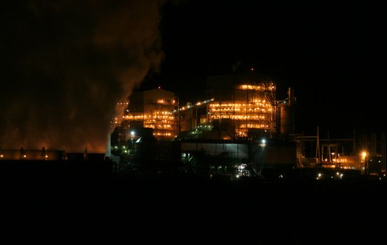 Factory with smoke stack at night