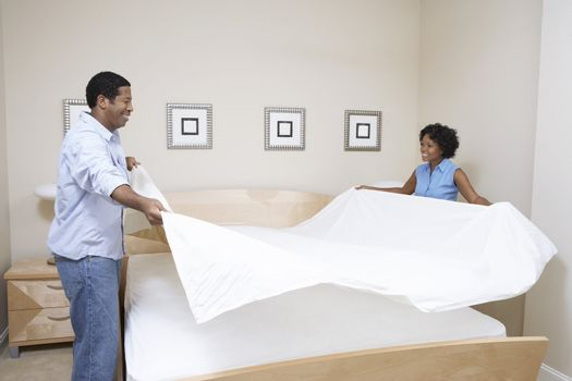 Couple Making Bed