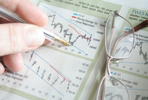 Hand with pen marking stock charts