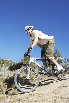Young Man Mountain Biking on Rugged Trail