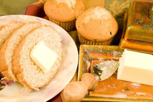 Bread slices and muffins with butter and plate