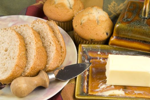 Bread and muffins with butter pad and plate