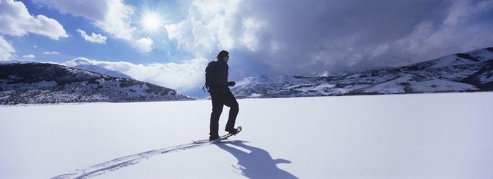 Man Hiking Through Snow