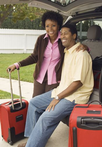 Couple and Luggage Standing by Minivan