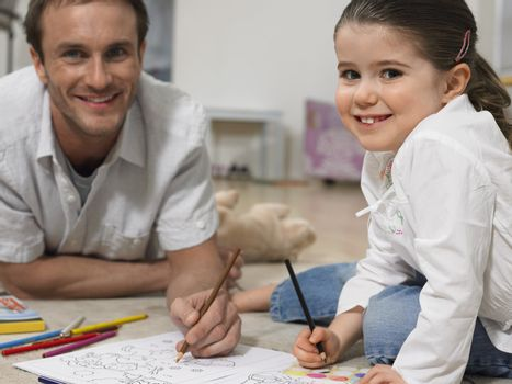 Father and Daughter Coloring Together on Floor
