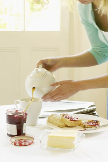 Woman Pouring Tea at Breakfast