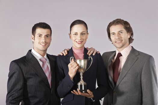 Businesswoman and Businessmen Holding Trophy