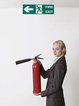 Businesswoman Holding Fire Extinguisher Under Exit Sign