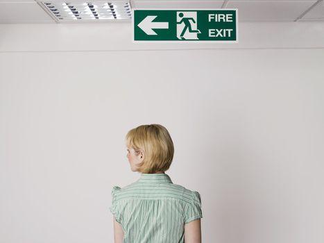 Businesswoman Standing Under Exit Sign