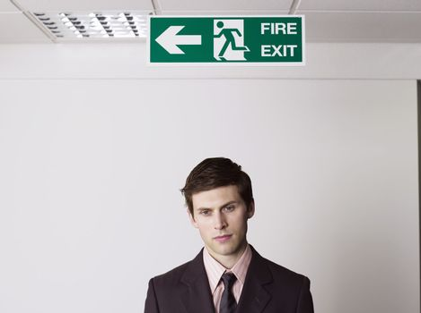 Businessman Standing Under Exit Sign