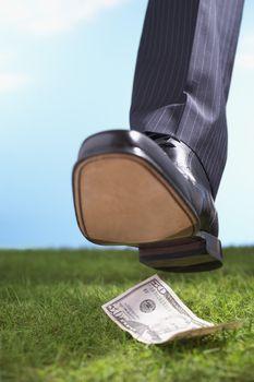 Businessman Stepping on 50-Dollar Bill