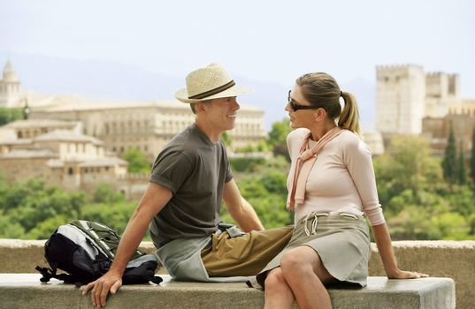 Tourist Couple Relaxing on Wall