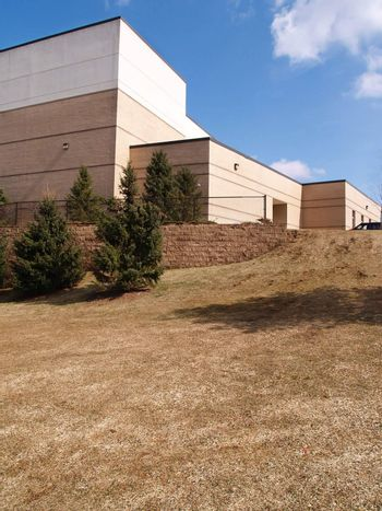 evergreen trees and a sloping lawn by a modern building with a blue sky in the background