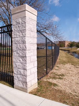 a stone cornerpiece and black fence