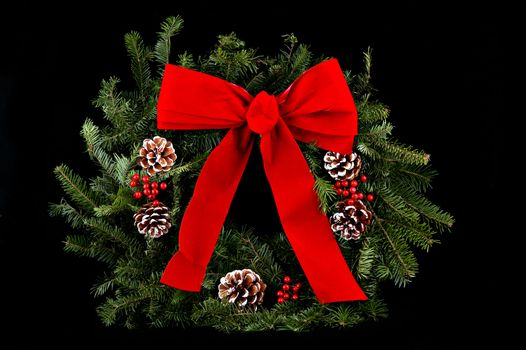 A Christmas wreath with red bow & decorative pine cones over black background.