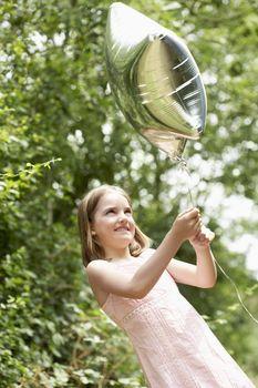 Girl Playing with Mylar Balloon