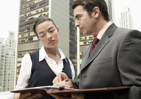 Businesspeople Outdoors Looking at Paperwork