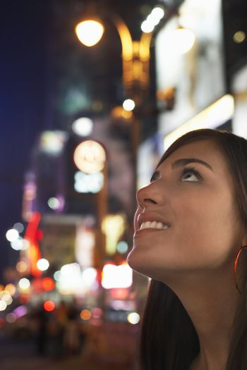 Young Woman on Sidewalk Looking Up