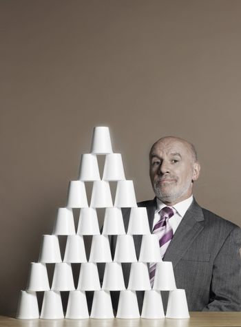 Businessman Building Pyramid of Cups
