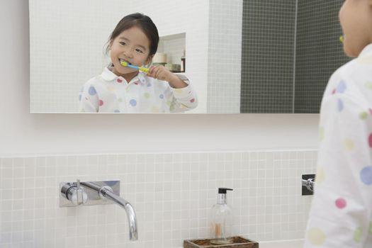 Reflection in Mirror of Girl Brushing Her Teeth