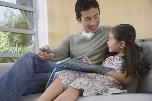 Man with Daughter Relaxing on Couch
