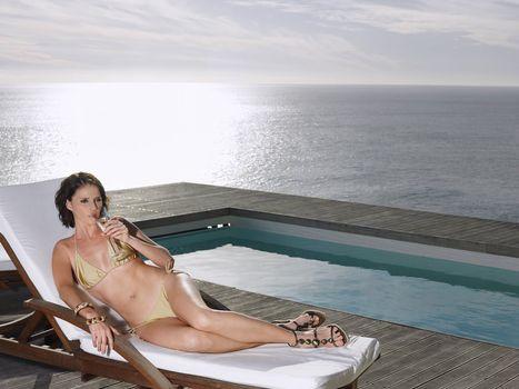 Woman in a Bikini Drinking Champagne