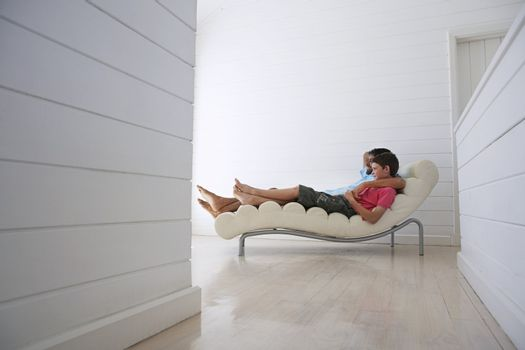 Father and Son Relaxing on Chaise Longue