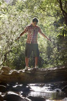 Young Man Balancing on Log