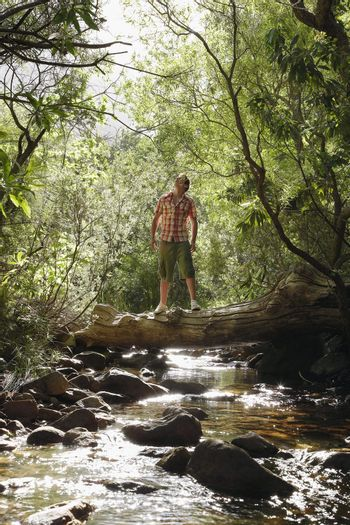 Young Man Standing on Log