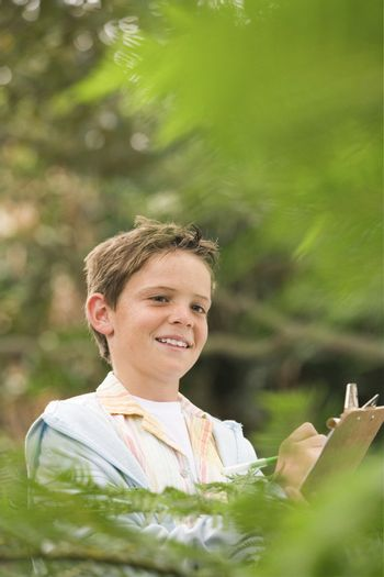 Boy Writing in Forest