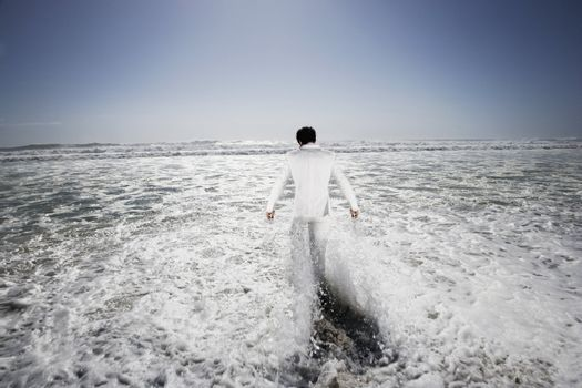 Businessman Walking into the Surf on the Beach