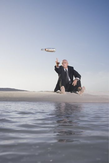 Businessman Tossing a Message in a Bottle into the Ocean