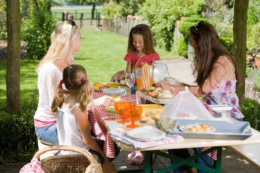 Mothers and their daughters having a picnic outdoors on a summer day