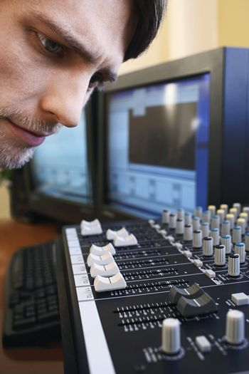 Man Looking at Levels on Mixing Board
