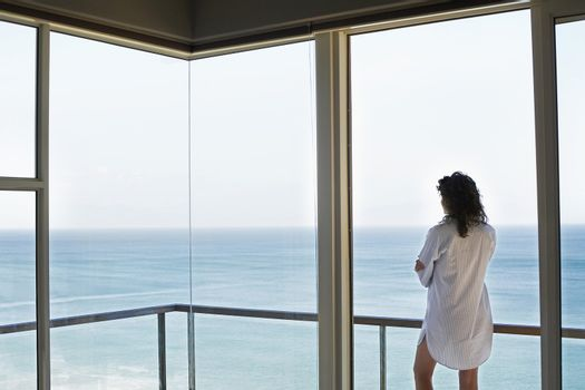 Woman looking at view standing on balcony back view