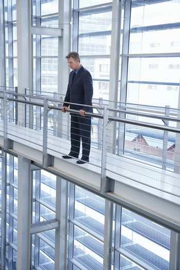Businessman Looking over Railing