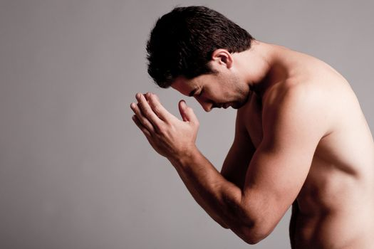 Shirtless man praying in the grey isolated background