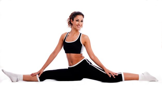 Fitness girl sitting and streching  her legs both sides on white background