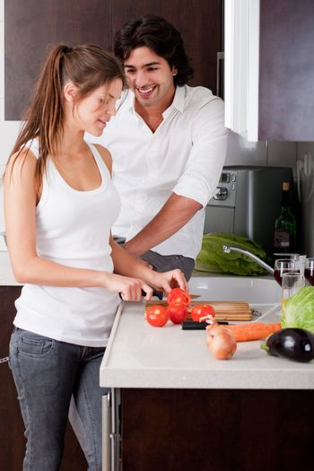 woman sliceing tomatoes with her boyfriend in kitchen