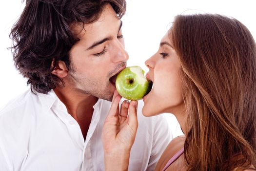 closeup of young couple playfully biting green apple